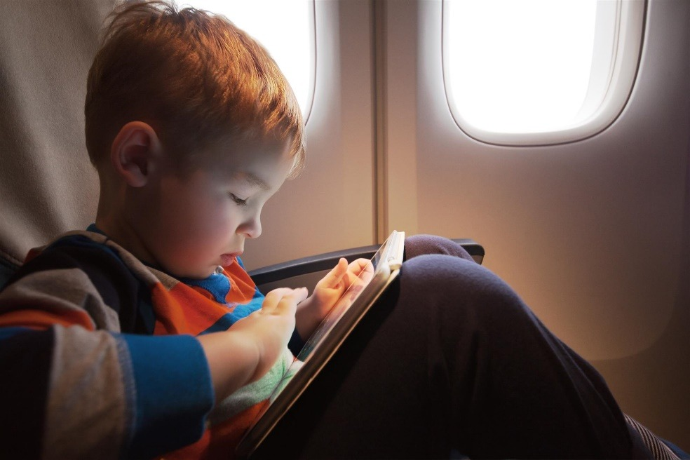 Child Aboard an Airplane with Tablet
