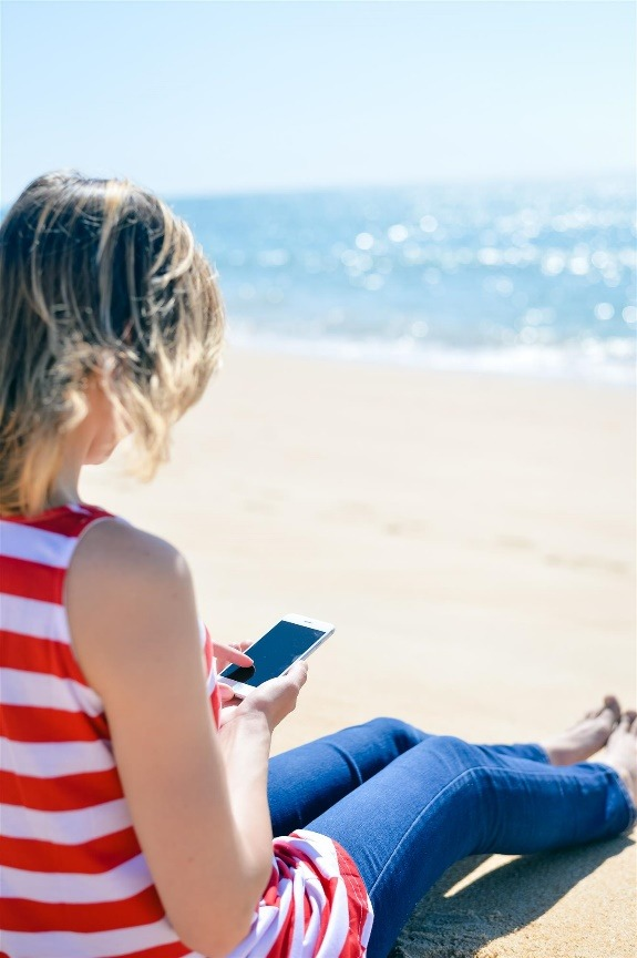 Girl with iPhone on Beach